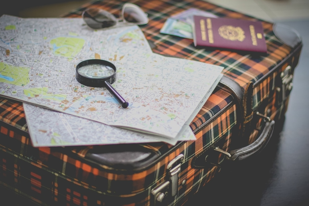 travel suitcase map and magnifying glass